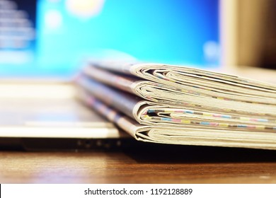 Stack of newspapers and laptop. Daily journals with news and personal computer. Tabloid papers with headlines  and articles and desktop on screen of electronic device. Different sources of information