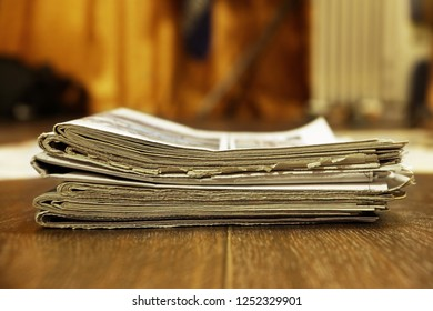Stack of newspapers. Old journals and magazines with news. Yellow pages with headlines and articles stacked in heap on wooden table. Business concept in vintage style
