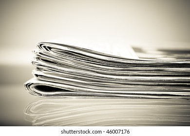 stack of newspapers on a glass table, vintage image