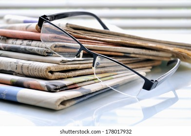 Stack of newspapers on office desk with glasses.