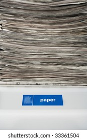 Stack of newspapers on a recycling bin