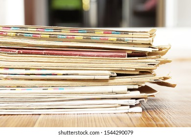 Stack of Newspapers on Wooden Table. News and Business Concept