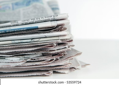 Stack of newspapers sit on a white background.