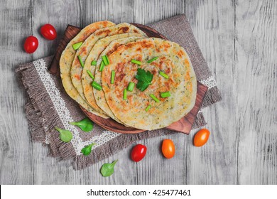 Stack of not sweet frying flour Flatbread Paratha roti, tortillas, cherry tomatoes, lettuce, napkin of burlap with lace, wooden board served on a light white surface, top view
