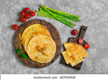 Stack of not sweet frying flour Flatbread Paratha roti, tortillas. Ingredients for Flatbread Paratha roti cherry tomatoes, asparagus, parsley, wooden board served on light gray background. Top view.
