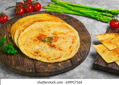 Stack of not sweet frying flour Flatbread Paratha roti, tortillas. Ingredients for Flatbread Paratha roti cherry tomatoes, asparagus, parsley, wooden board served on light gray background.