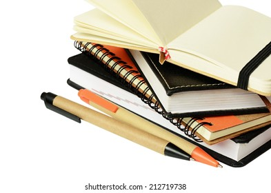 Stack of notebooks and pens isolated on white