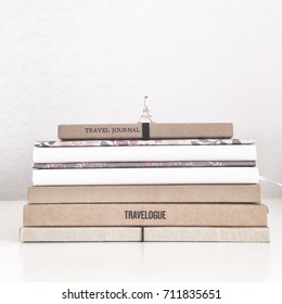 Stack of notebooks and travel journals on a white shelf with a wooden figure of the Eiffel Tower on it