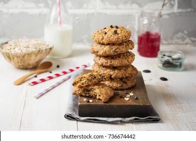 Stack of oatmeal cookies with chocolate on a light background with flakes and a bottle of milk. Selective focus.