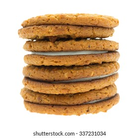 A stack of oatmeal frosting filled cookies isolated on a white background.