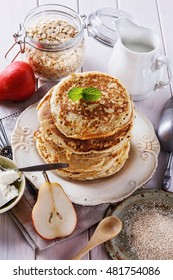 Stack of oatmeal pancakes for breakfast over white wooden background