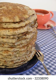 a stack of oatmeal pancakes on a blue plate with an orange cup of tea in the background