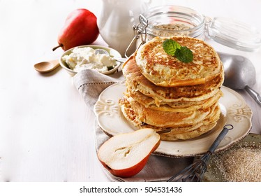 Stack of oatmeal pancakes over white background close up