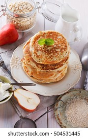 Stack of oatmeal pancakes over white wooden background close up