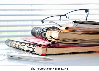 Stack of office folders with glasses and ballpoint in front of a window