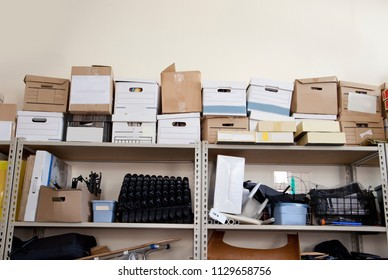 A stack of office supplies piled high in a storage room includes bankers boxes