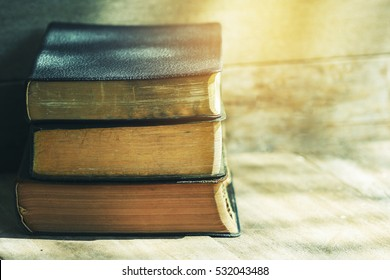 stack of old bible on wooden background with widow light, vintage tone and light effect, copy space