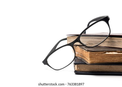A stack of old books with eyeglasses on a white background. Free space for text