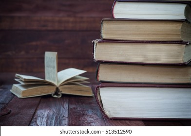 stack of old books on brown wooden surface near the open book, vintage style