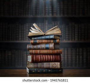 A stack of old books on table against background of bookshelf in library. Ancient books as a symbol of knowledge, history, memory and information. Conceptual background on education, literature topics - Shutterstock ID 1945761811