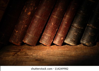 Stack of old books in a row on wooden surface