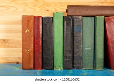 a stack of old books standing side by side on a shelf, wooden background. front view