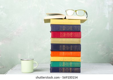 A stack of old color books, glasses and a cup of tea on a table and a green background