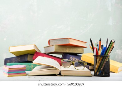 A stack of old color books, glasses, stationery on a table and a green background