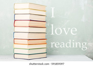 "A stack of old colored books on shelf and green background with text ""I love reading"""