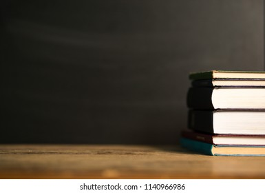 Stack old hardback books on wooden deck table and dark background