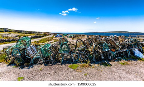 Stack of old lobster / crab cages or fishing traps found on the coast on Inis Oirr island, the ocean in the background on a sunny day in Inisheer, an island in the west of the coast of Ireland