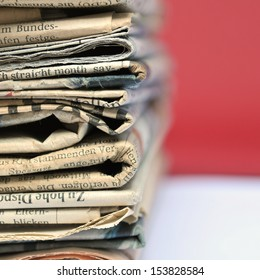 Stack of old newspapers with red background