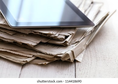 Stack of old newspapers and a tablet pc on the wooden table