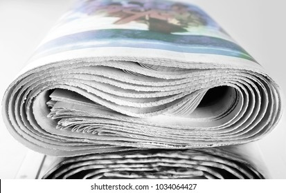 A stack of old rolled up newspapers
