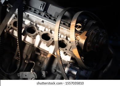 Stack of old timing belt and car engine.Automobile spare parts with sunlight.Car accessories in the garage.Car service, repair, maintenance concept.