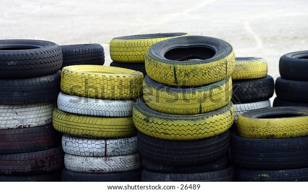 A stack of old used colored car tyres