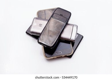 Stack of old used mobile phones isolated on white background
