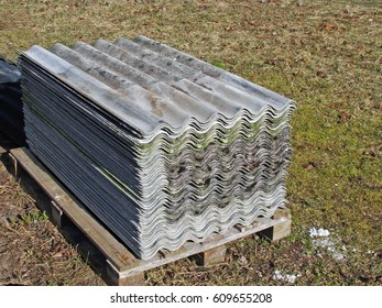 Stack of old used wavy asbestos roof tiles sheets outdoor on wooden pad