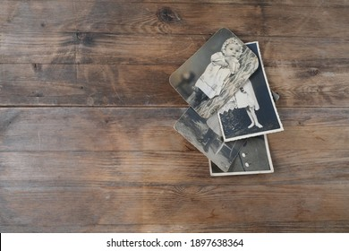 stack of old vintage monochrome photographs 1960 on photographic paper on natural wood background, concept of genealogy, the memory of ancestors, family tree