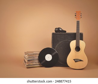 A stack of old vinyl records and acoustic wooden guitar with an amplifier are isolated on a brown background for a music or band concept.