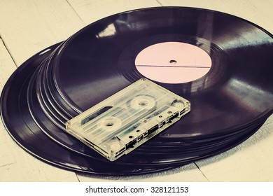 Stack of old vinyl records and audio cassette on white wooden table. Toned photo