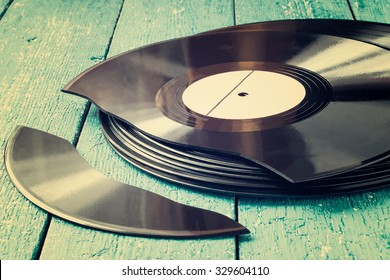 Stack of old vinyl records on a blue wooden background, one record broken. Toned photo