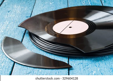 Stack of old vinyl records on a blue wooden background, one record broken