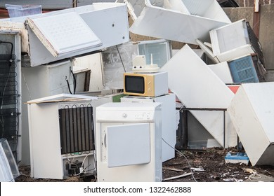 A stack of old white electrical household appliances waste such as a fridge or microwave, ecologically disposed of in a landfill (dump, collection yard). of hazardous waste.