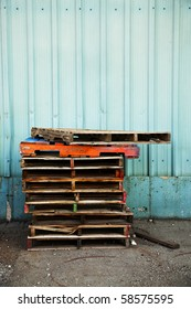 A stack of old wooden pallets painted in bright colors, next to the blue corrugated metal wall of an old factory building.