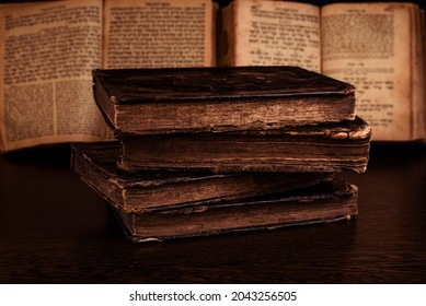 Stack of old worn shabby jewish books in leather binding and open blurred Torah in the background in the dark. Closeup. Selective focus