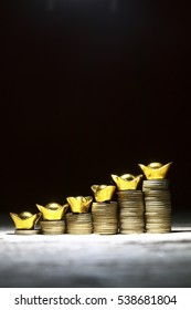 Stack on coins with gold ingot showing growth
