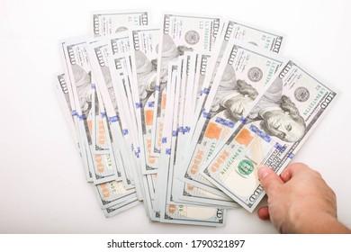 Pile de billets de cent dollars à la main sur fond blanc.