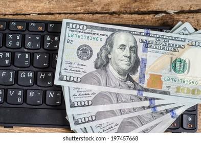 Stack of one hundred dollar bills  on keyboard