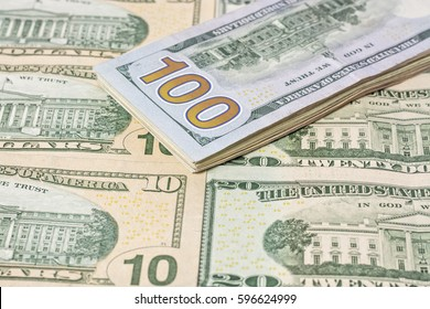 A stack of one hundred dollar bills on a background of dollars